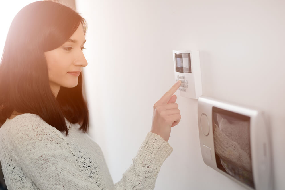 A young woman turning on alarm system which may be a factor that affects home and contents premium