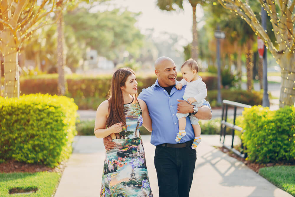 Two parents with young child walking outside among trees and greenery