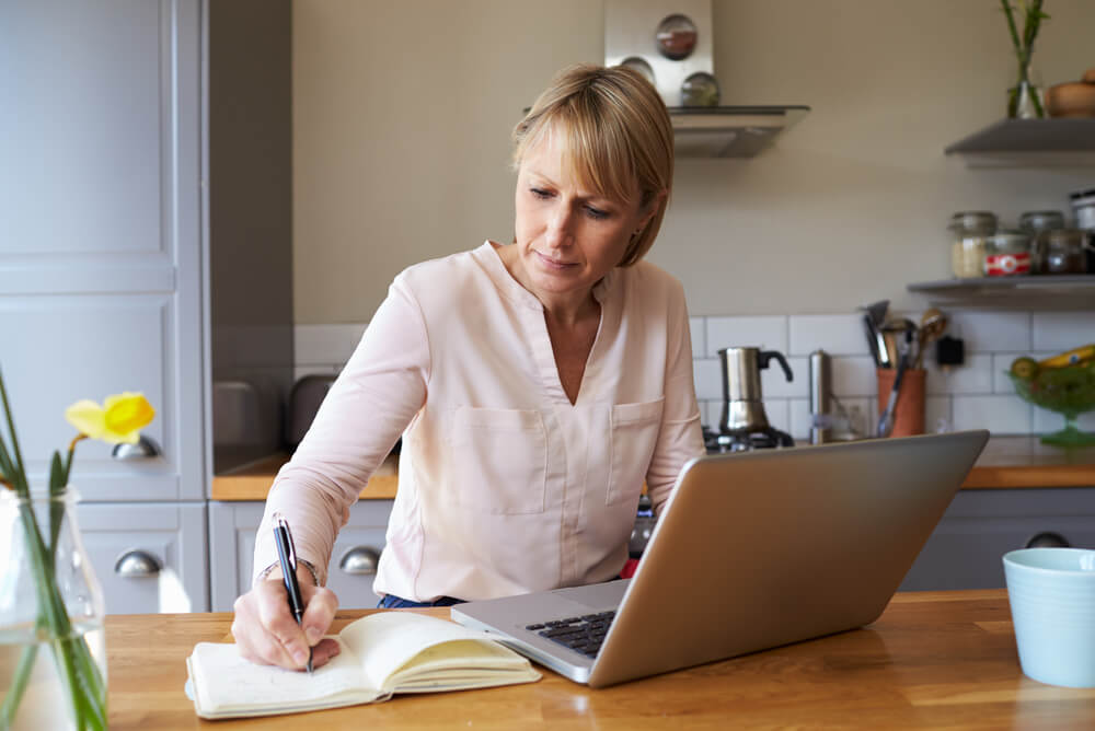 woman in her kitchen writing a list of her contents for insurance purposes