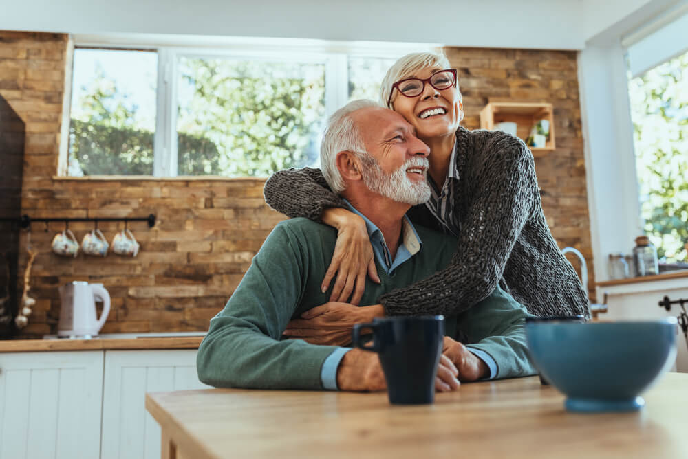 Older couple embracing in kitchen