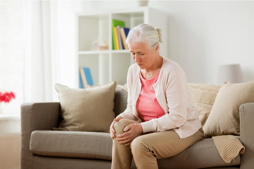 Older woman clutching knee in pain wondering if she's covered by gold health insurance