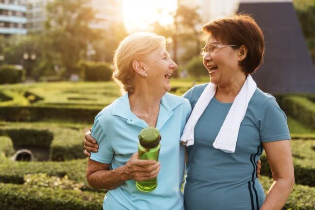 two older women dressed in workout clothes and smiling while exercising outdoors