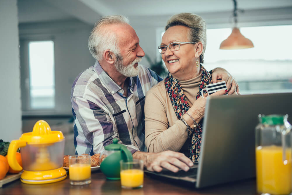 an older couple using a laptop on the kitchen bench