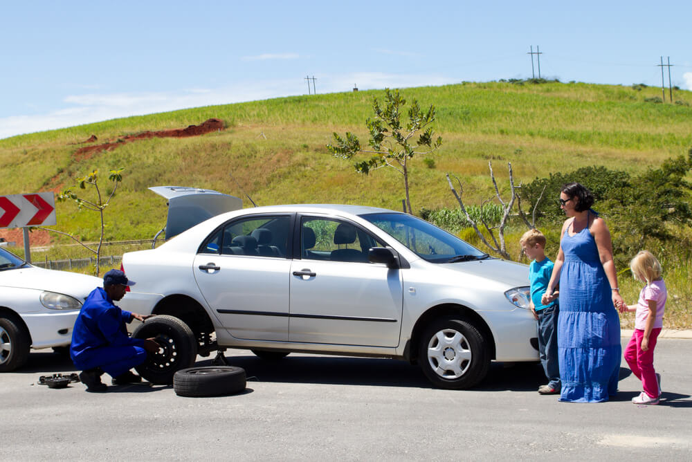 Mum and two kids wait while roadside assistance fixes their car