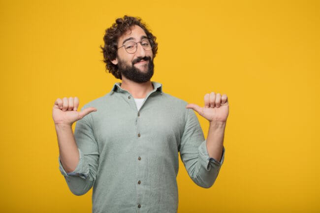 Man with glasses pointing thumbs at chest