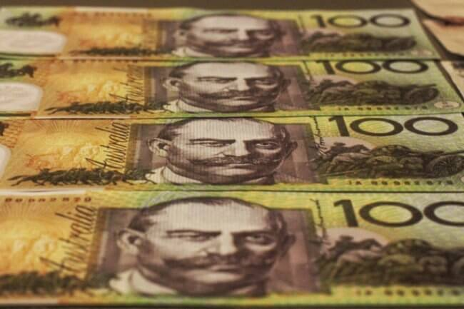 Four Australian $100 notes laid out in a row