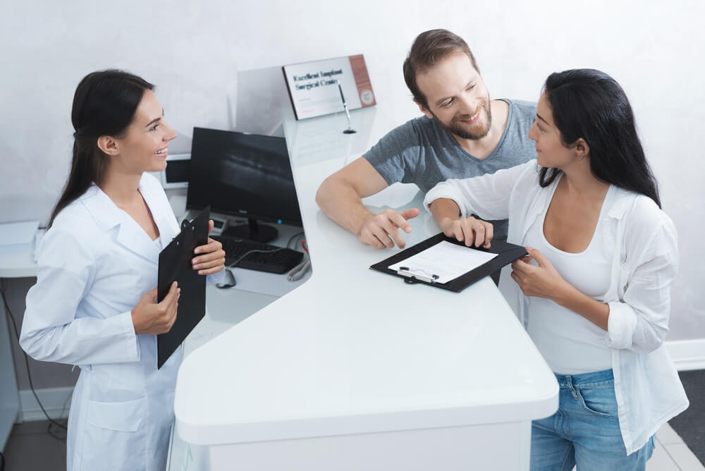 man and woman visiting dental clinic asking how much they can claim on dental insurance