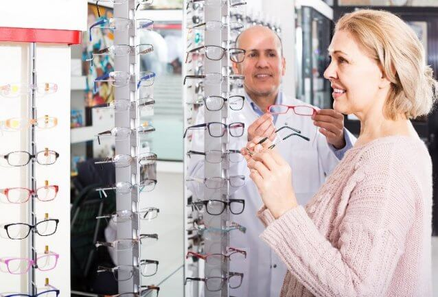 Couple looking for glasses at an optical store
