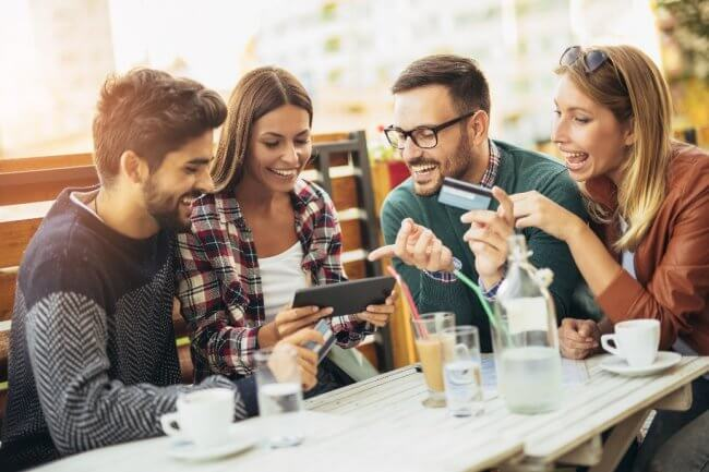 Four friends purchasing something on a tablet with a credit card