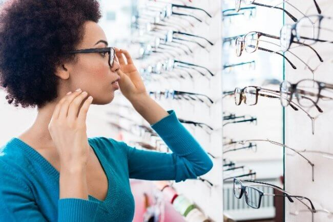 Woman trying on glasses at an optical store