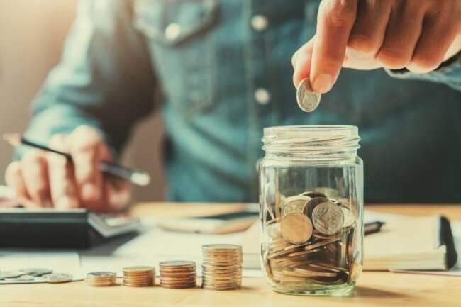 man putting coin into a savings jar