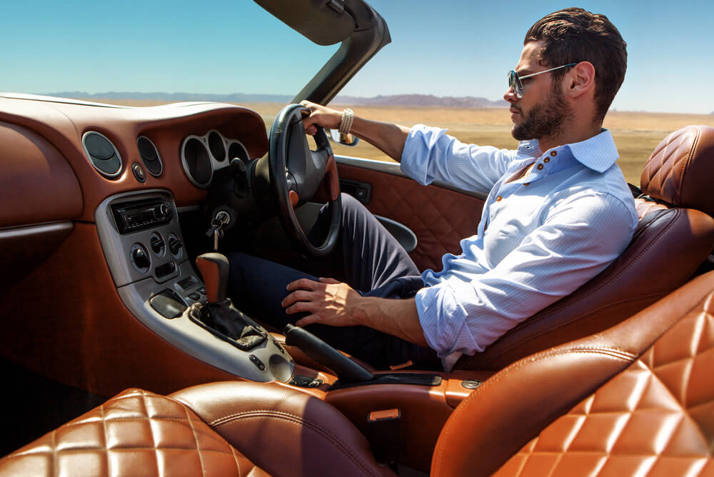 Man driving prestige luxury car