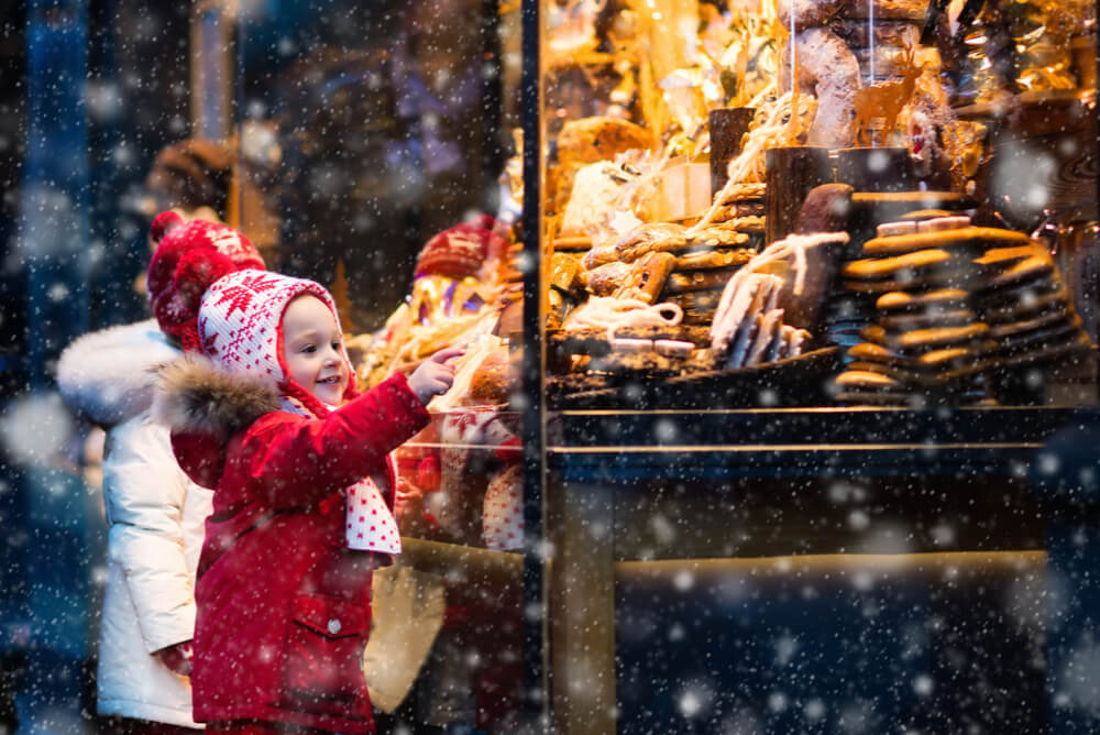 children looking at sweets displayed in a Christmas market
