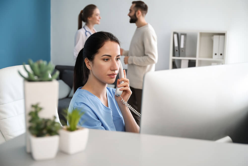 Medical receptionist speaking on the phone