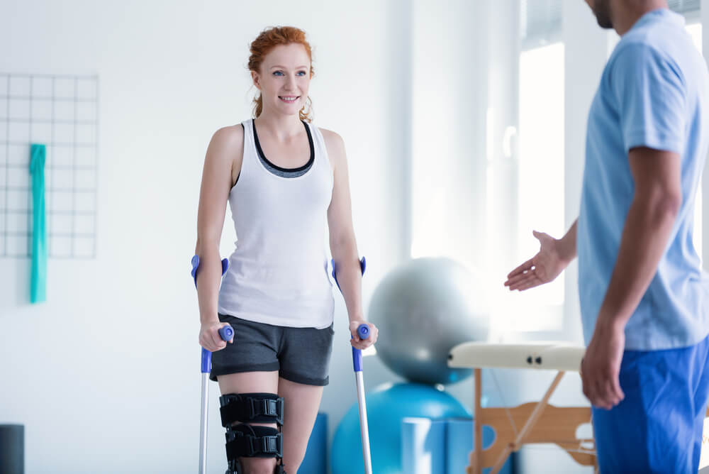 a female patient on crutches walking towards a physiotherapist