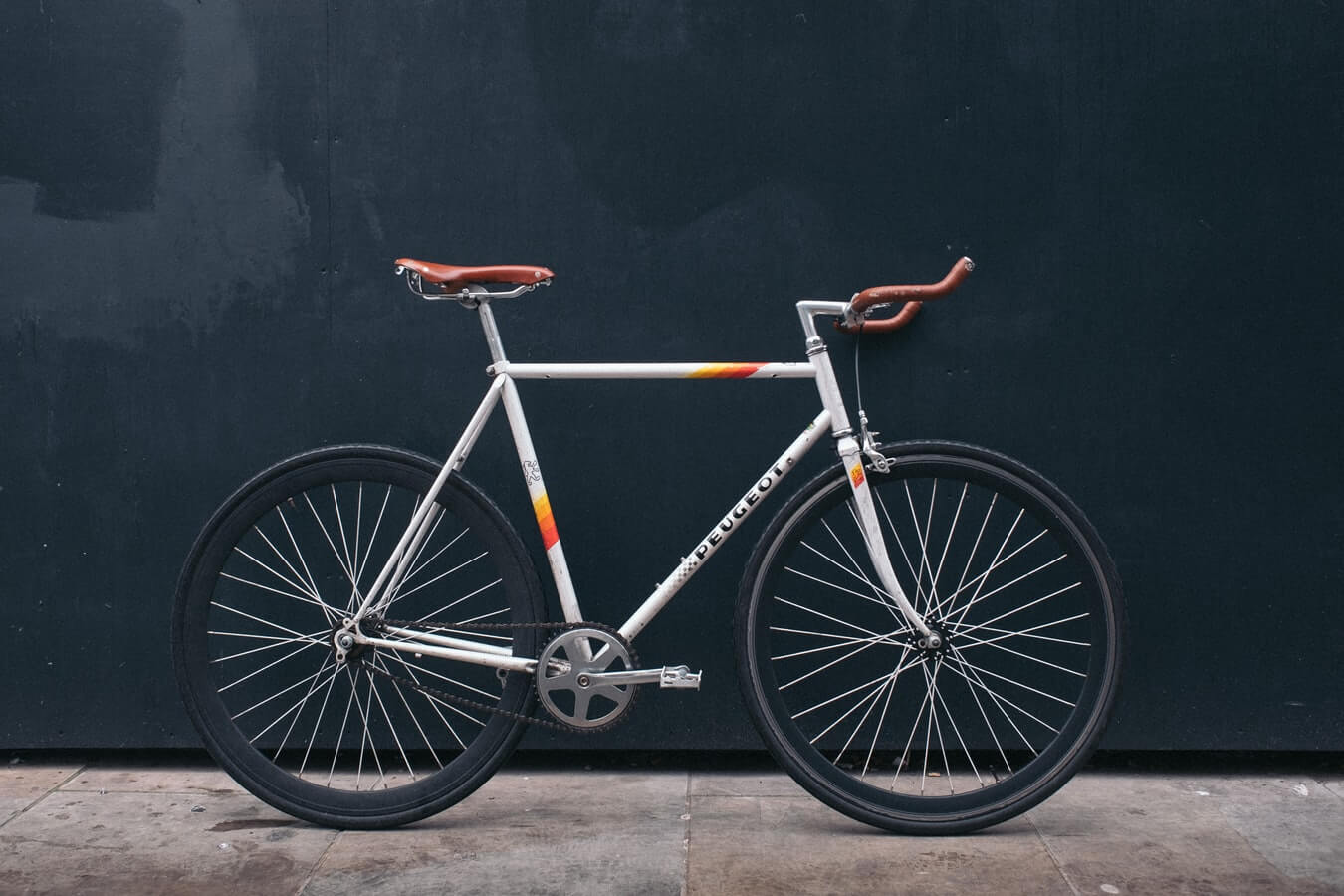 a bicycle against a black wall