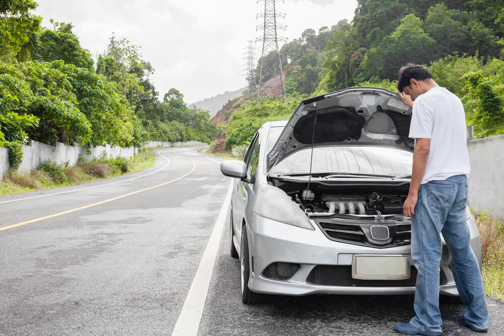 A man looking at the engine of his broken down car.