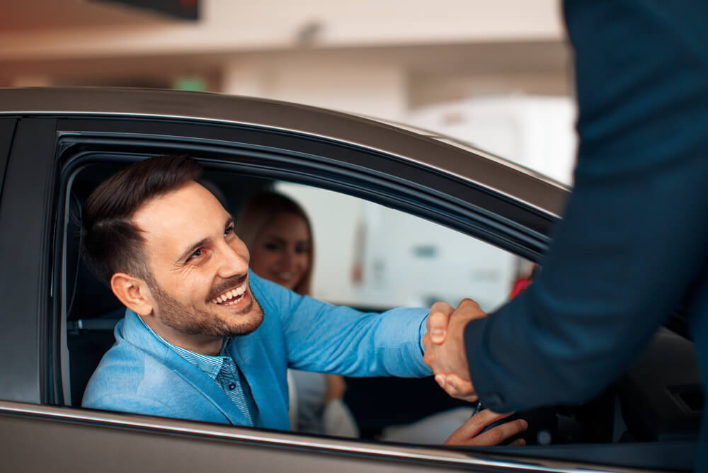A man sitting in a car shakes someone's hand