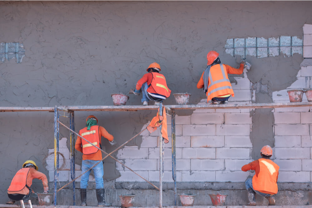 Construction workers plastering a wall.