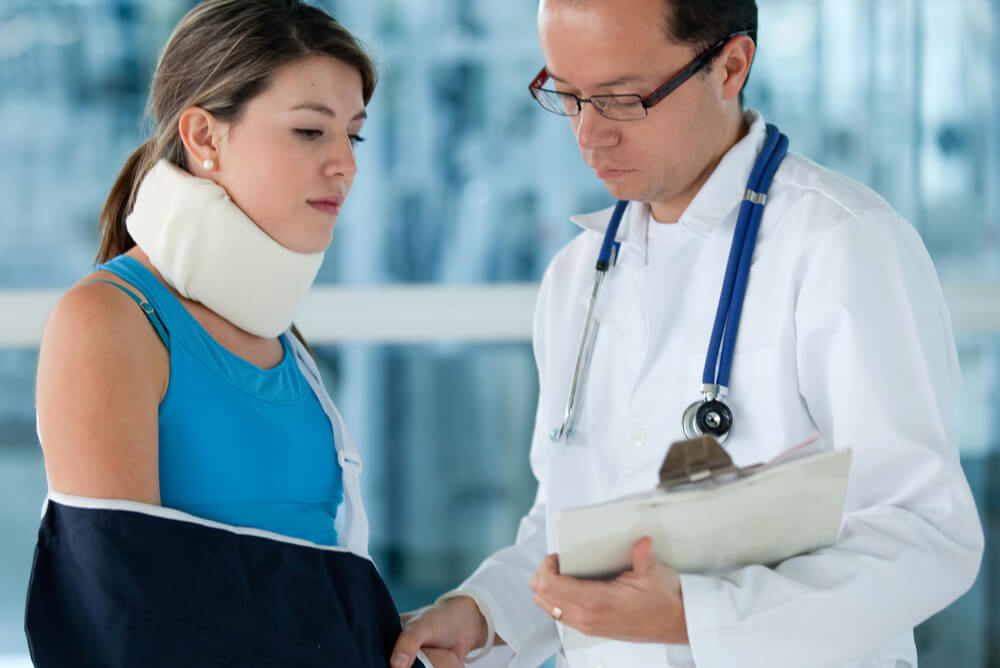 Doctor helping business owner with broken arm