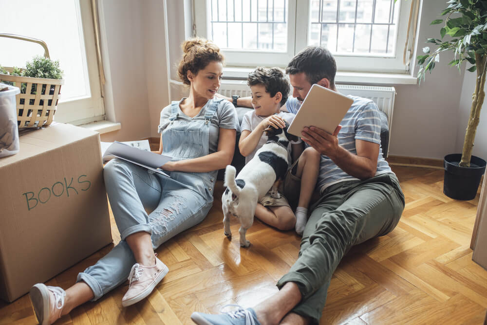 A family of three sitting on the floor of their new home with a dog