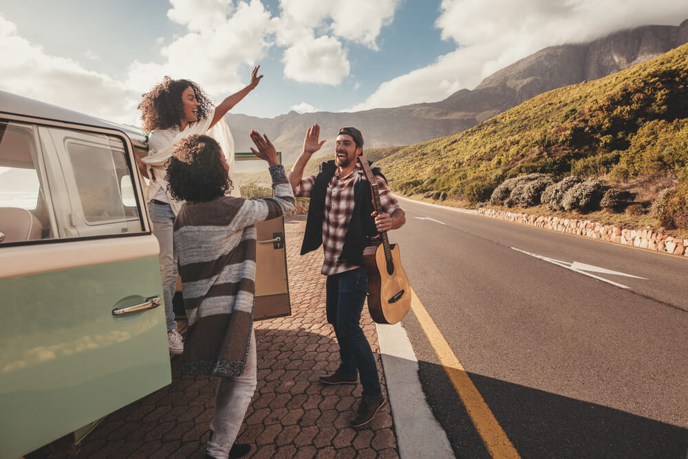 A group of friends on a road trip standing in front of a van highfiving,