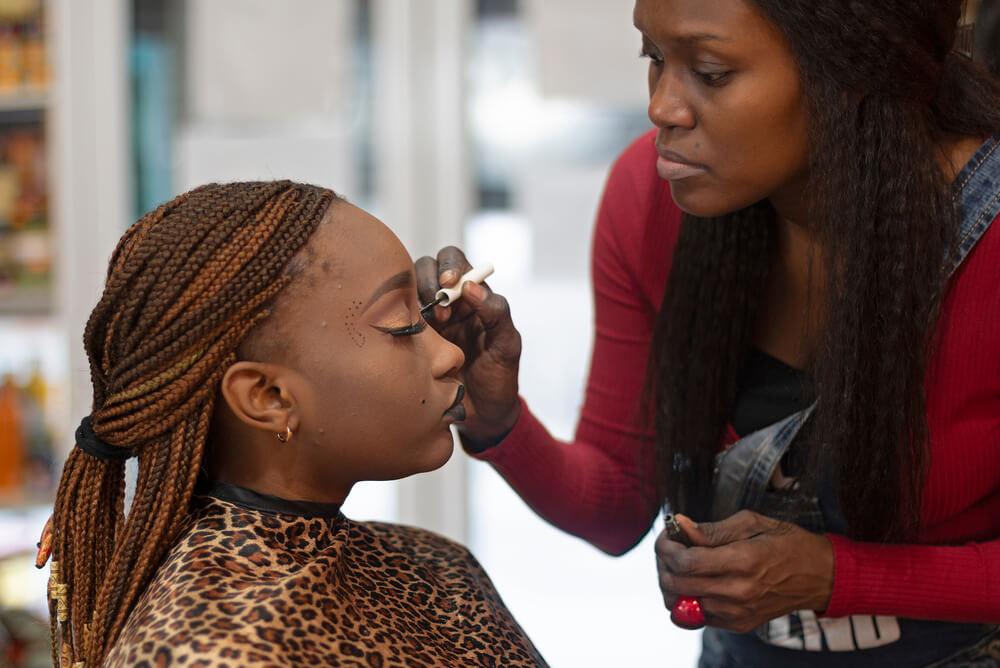 Makeup artist applying makeup to client