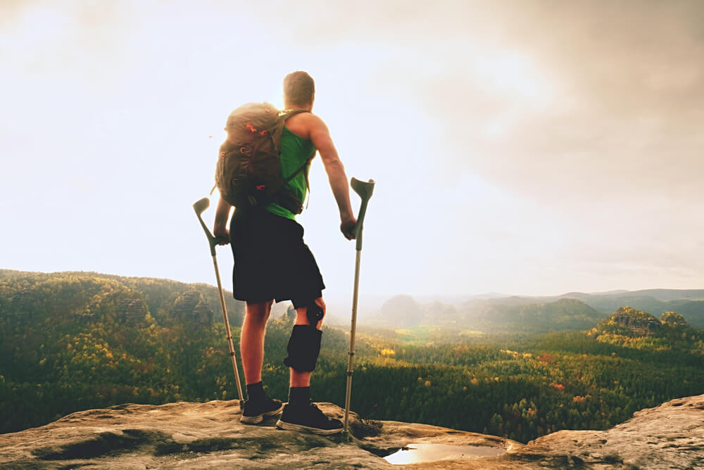 Man with an injured leg hiking to the top of a mountain