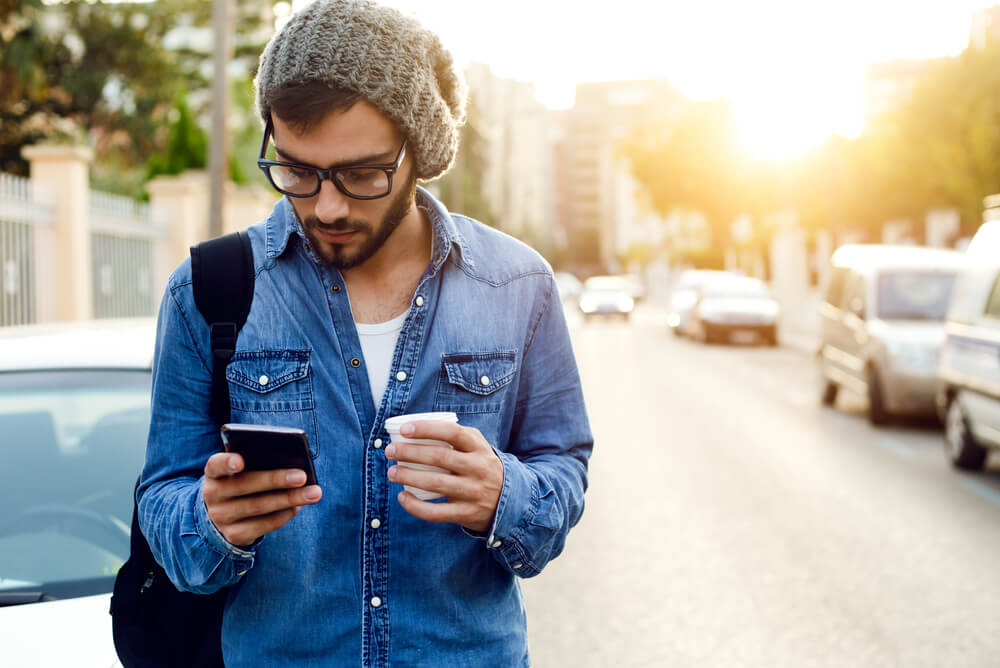 Man using phone to time smart appliances