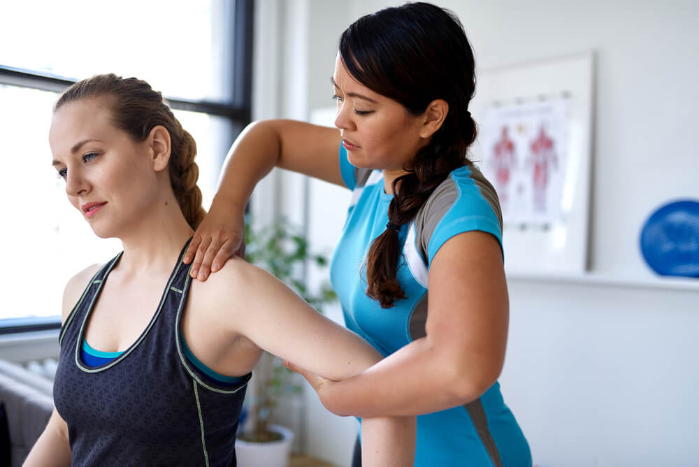 physiotherapist working with female client
