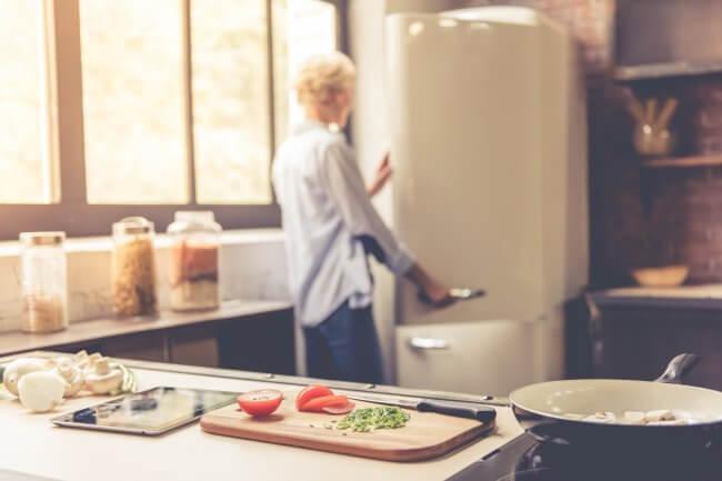 woman looking in old fridge
