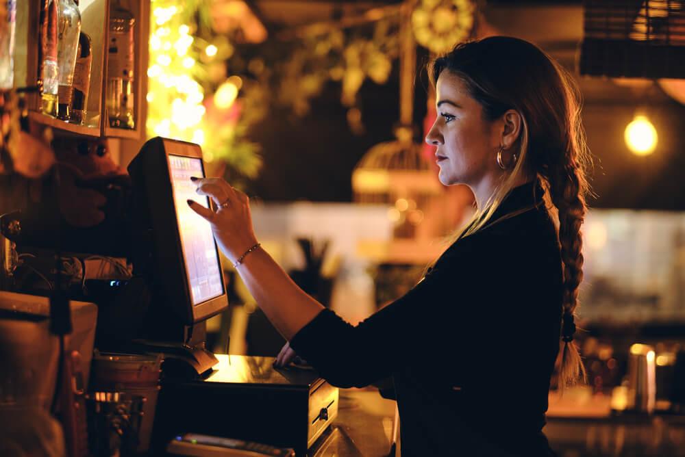 a waitress processes an order at the cash register of a bar