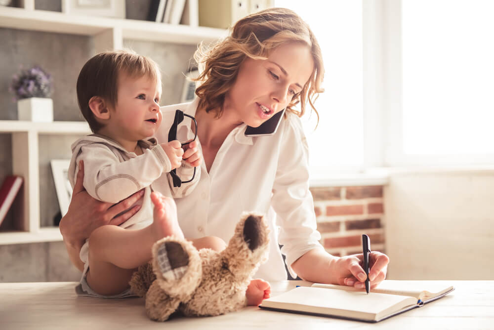 mum holding baby while talking on phone and working from home