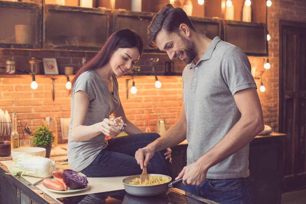 a couple cooking dinner in their apartment building