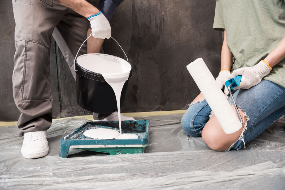 a couple pouring paint into a tray