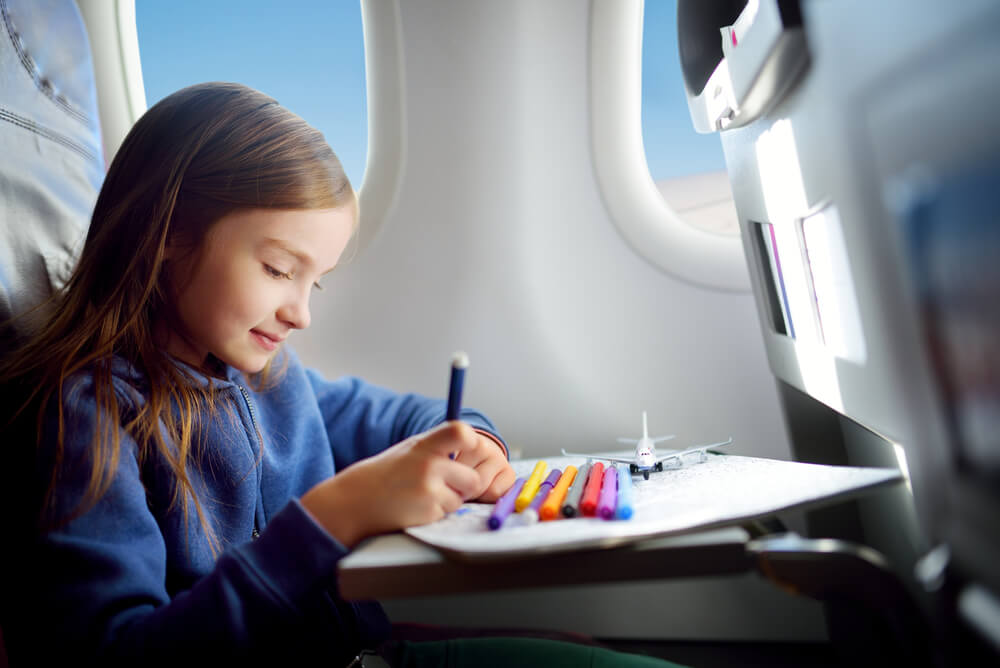 a girl colouring-in while flying on a plane