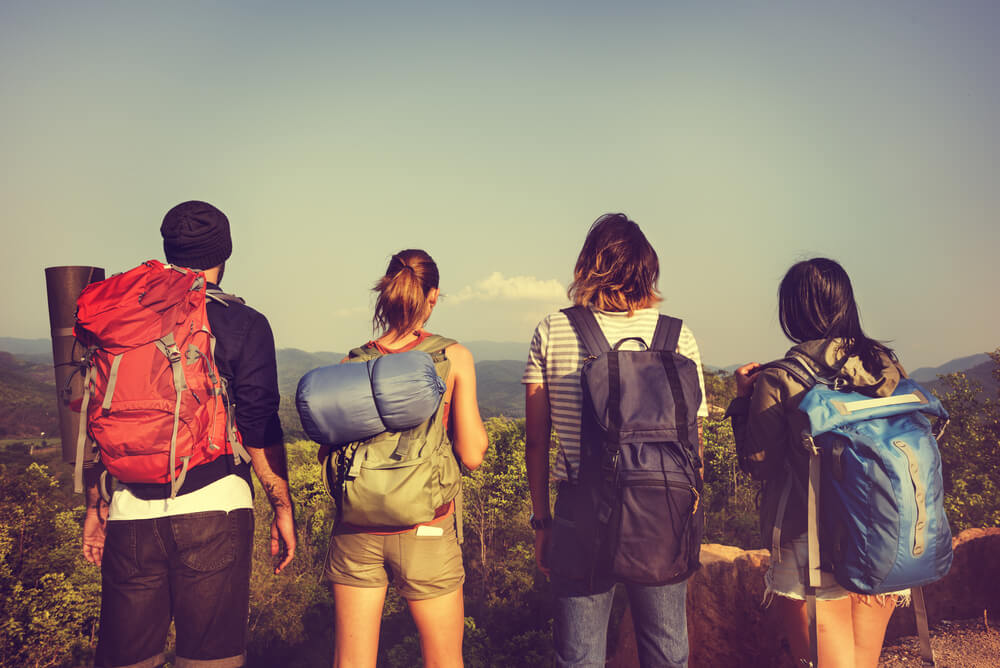 group of backpackers at the beach with travel insurance