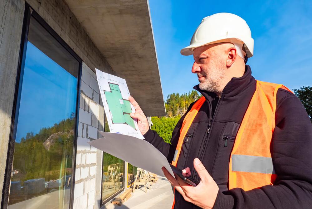 a man inspecting a wall under construction