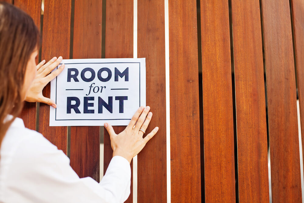 a woman putting up a room for rent sign