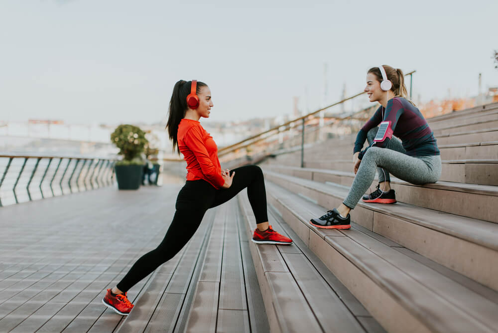 two young women exercising on steps with headphones on