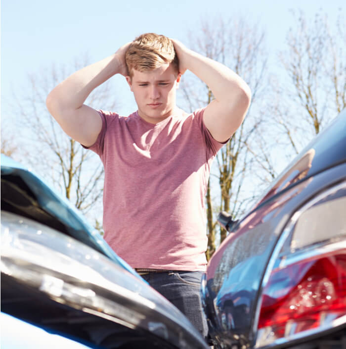 a young blonde man inspecting a car accident