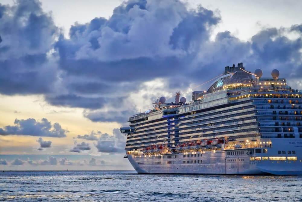 a cruise ship at dusk on the ocean