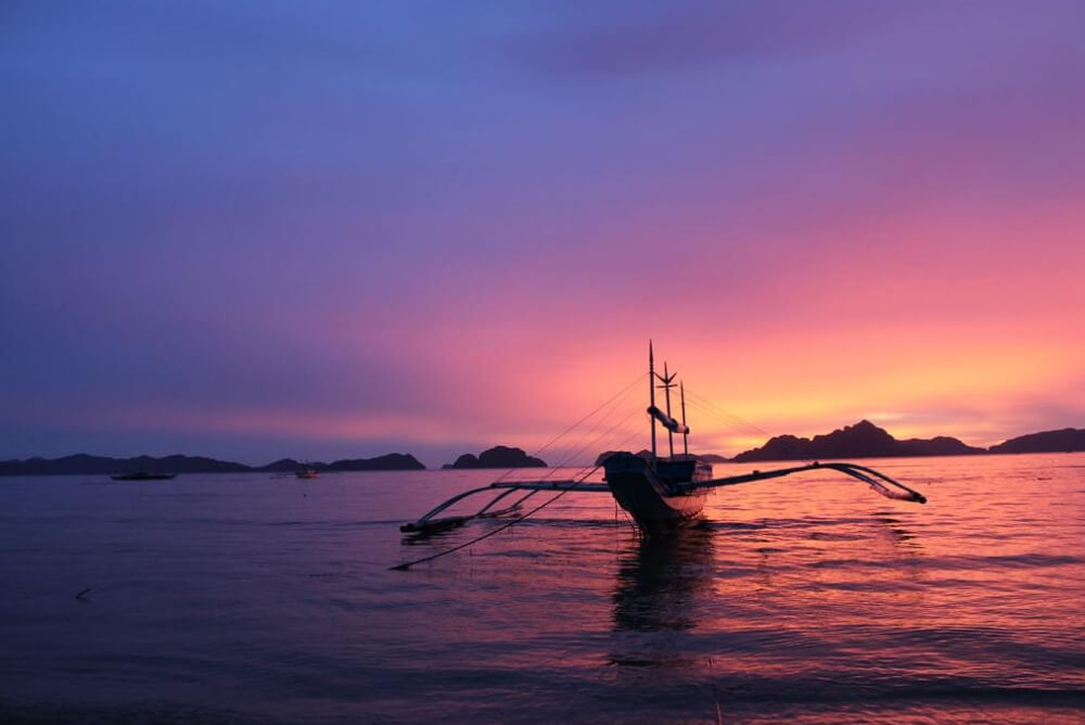 a boat on the waters at El Nido in the Philippines at sunset