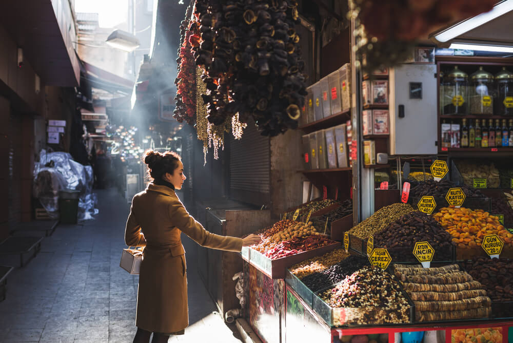 a woman shopping at a market in Istanbul's Grand Bazaar