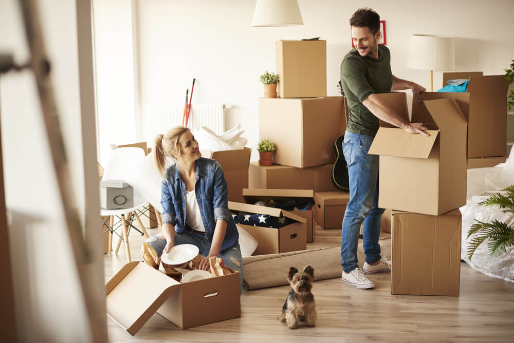 a couple moving into their new home with their pet