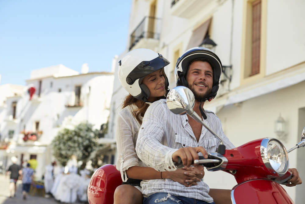 a couple riding on a scooter together through the streets of BIiza, Spain