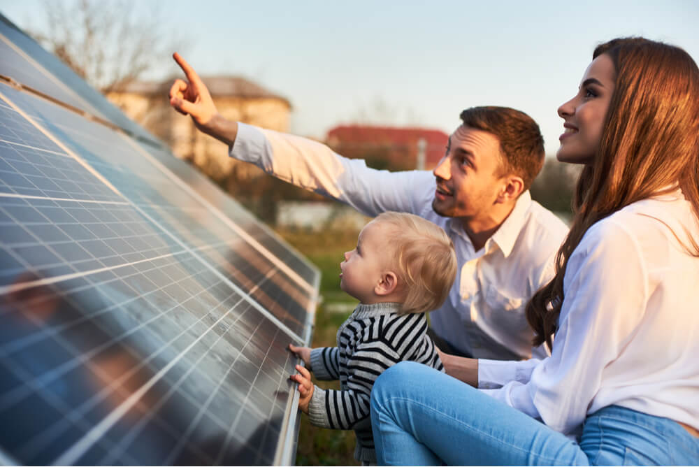 a family inspects a solar panel