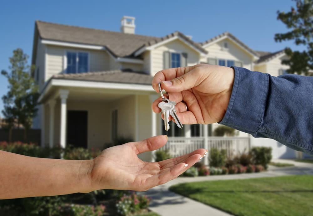 A landlord handing over keys to his house.