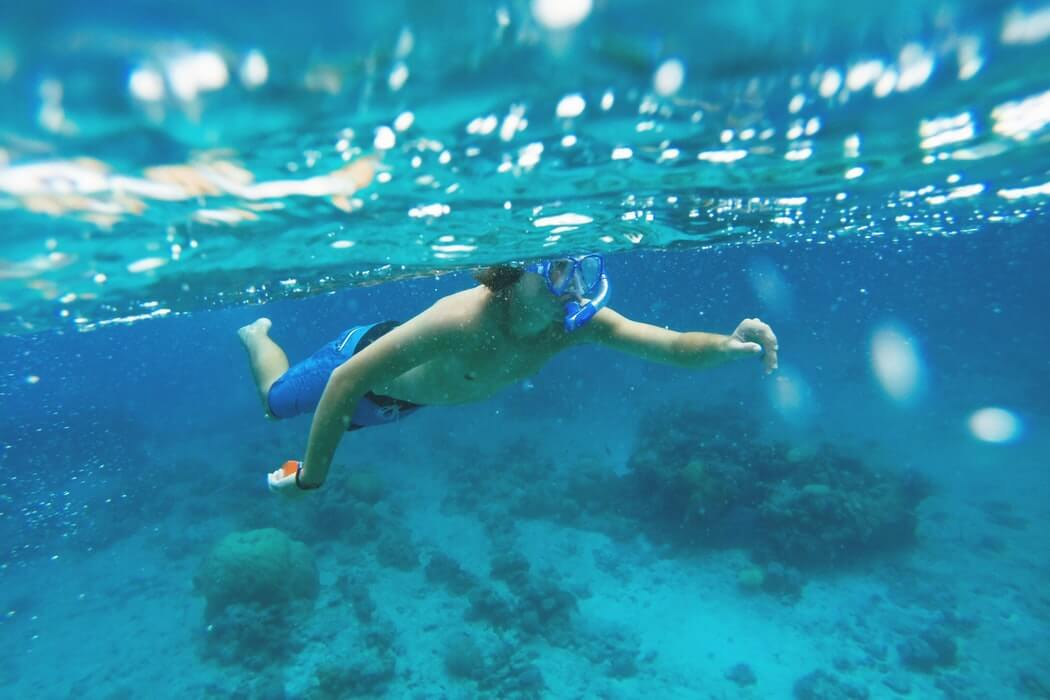 a man snorkelling over the reef at Lifou Island, New Caledonia