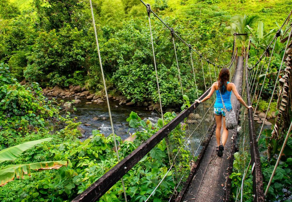 A woman walking over a suspension bridge in Fiji.